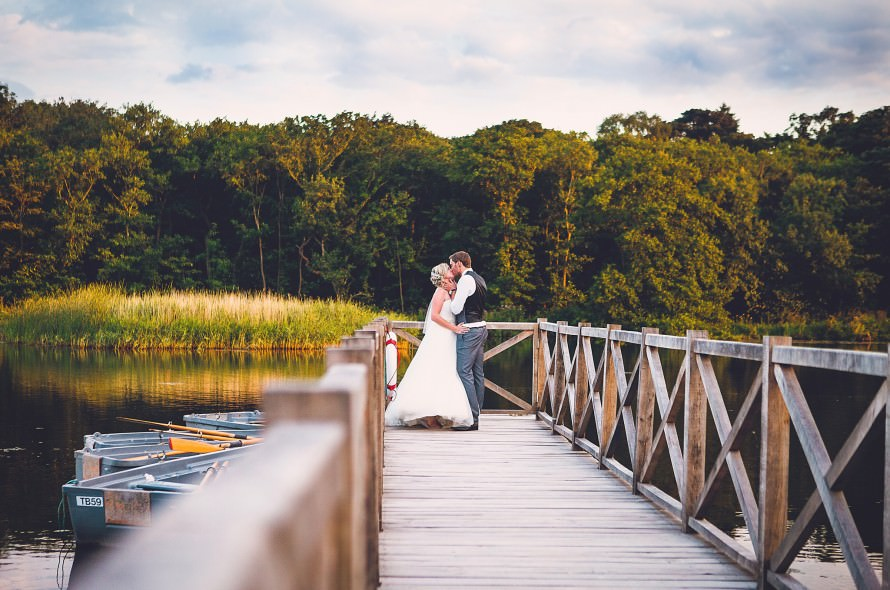 A bride and groom kiss on the jetty of the Boathouse Weding Venue in Norfolk as the sun sets