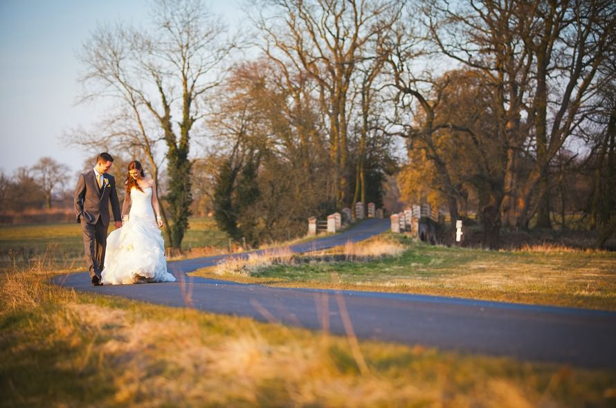 A newly wed Bride and Groom walk hand in hand in the evening light at a Norfolk Wedding