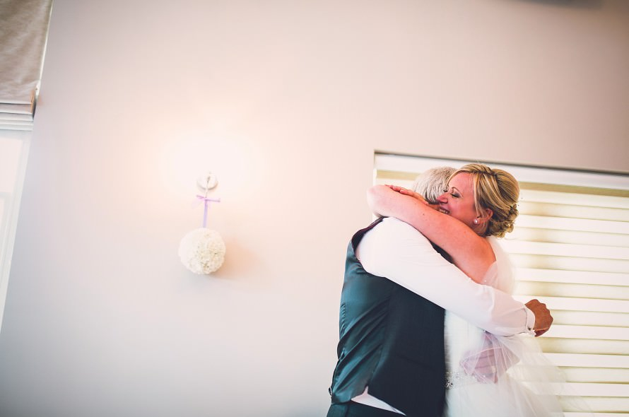 A bride hugs her father with tears in her eyes