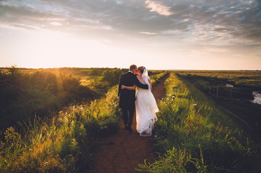 A bride and groom walking in the evening sun at Morston
