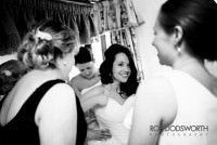 Bride smiling as she is helped into wedding dress