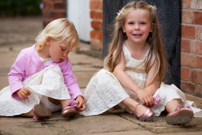 two little girls admiring their shoes at wedding
