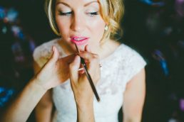 A bride having her lipstick applied before her wedding