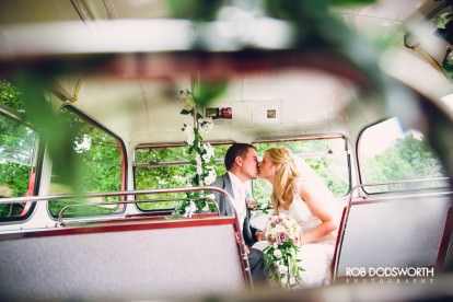 a bride and groom kissing on a routemasterbus on their wedding day in Norwich