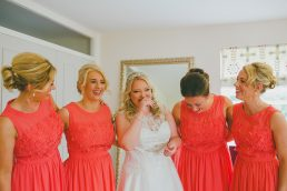 A bride and her bridesmaids laughing together at the Boathouse