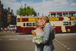 Couple kissing in front of London bus at a wedding