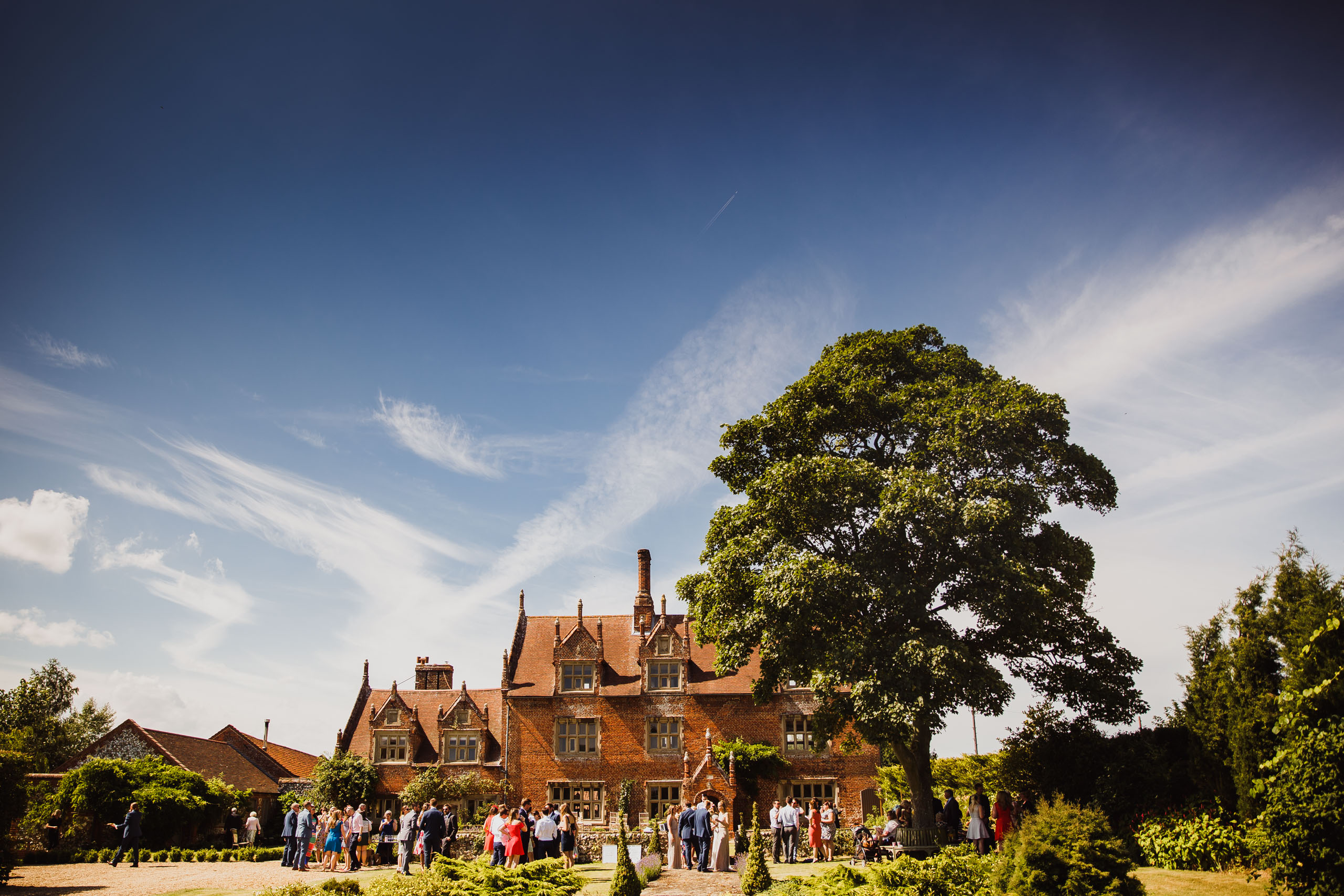 Wedding guests relax in the sun at a Hautbois Hall wedding