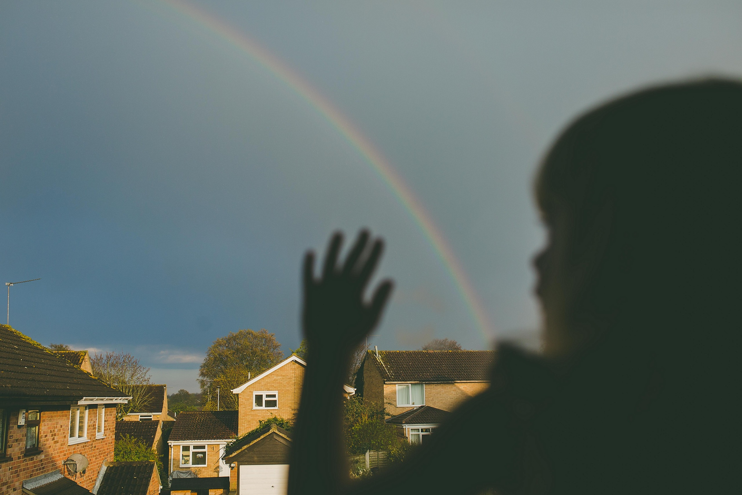 Child watching a rainbow form