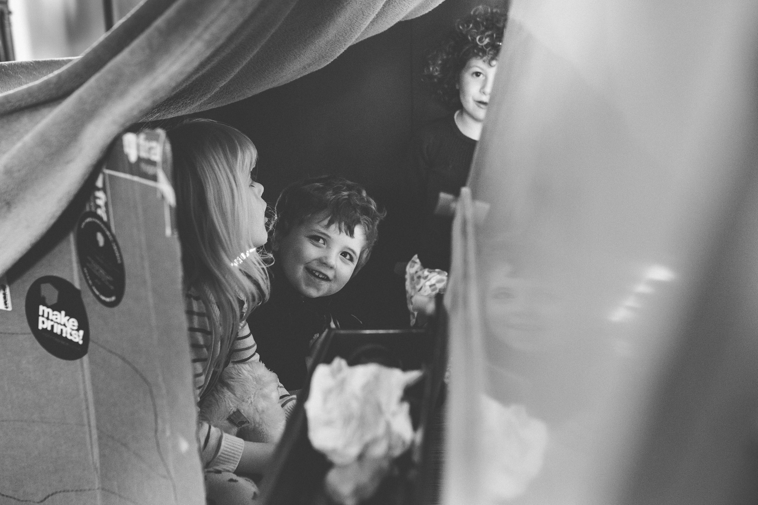 Black and white photograph of children playing in boxes by Norfolk Family photographer Rob Dodsworth