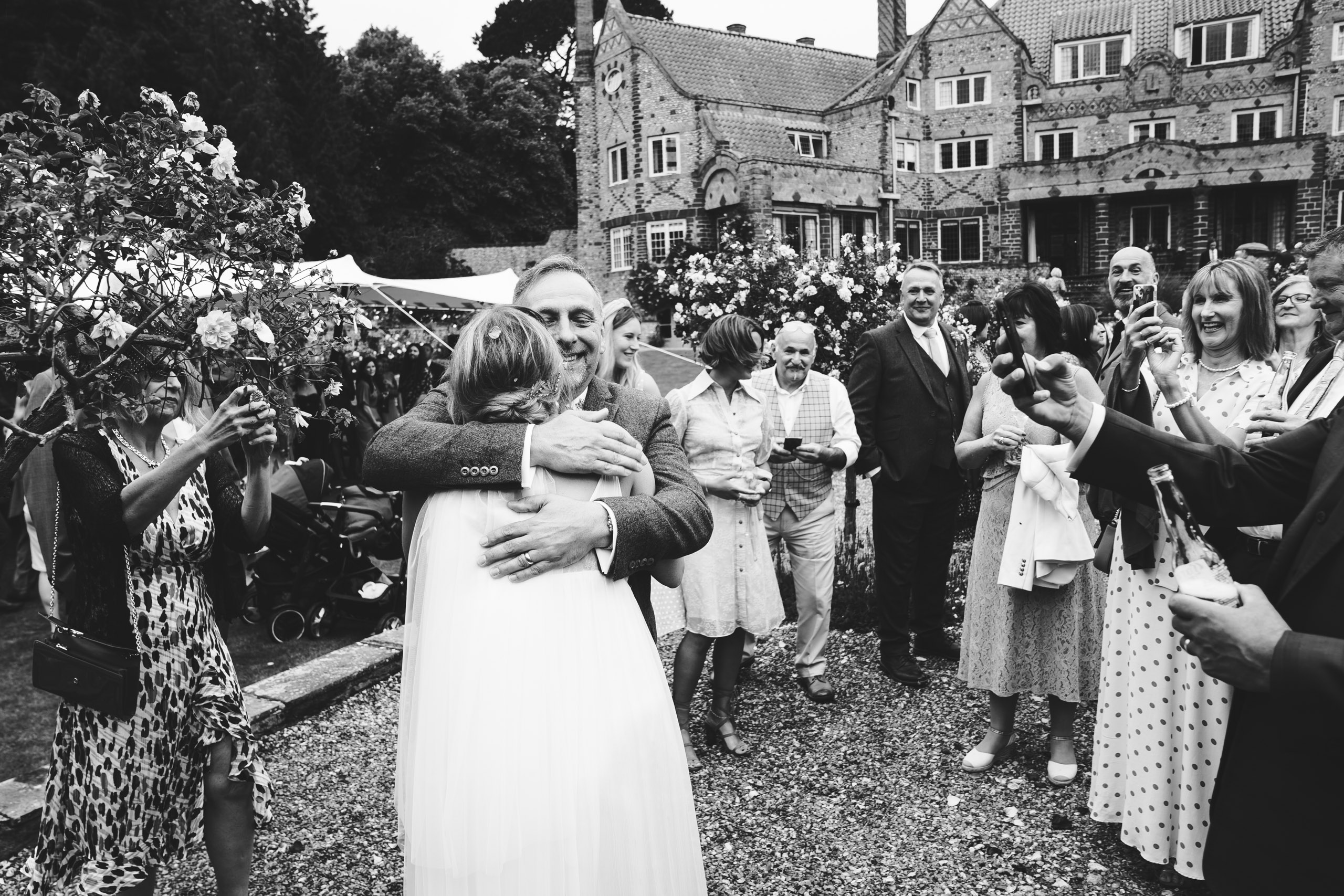 father of the bride hugs his daughter with voewood in background
