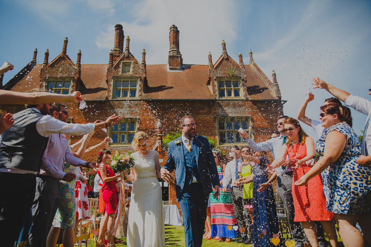 Bride and groom exit their wedding at Hautbois Hall to a shower of confetti