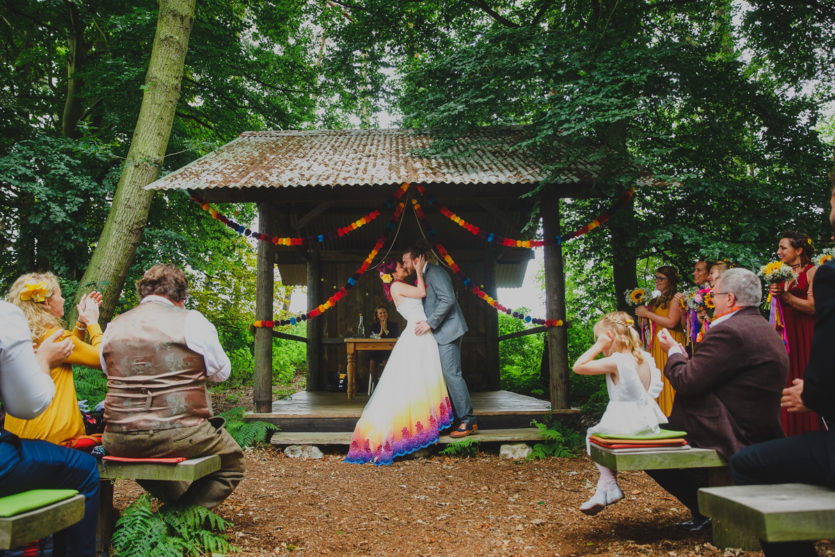 Bride and groom kiss under the woodshed at a Hush venue wedding in norwich