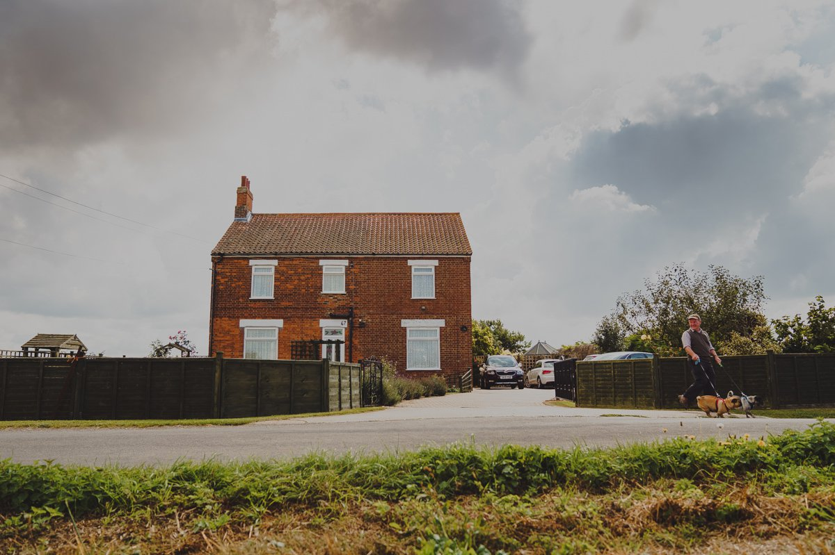 A man walks his dogs by a detached farmhouse in West Norfolk