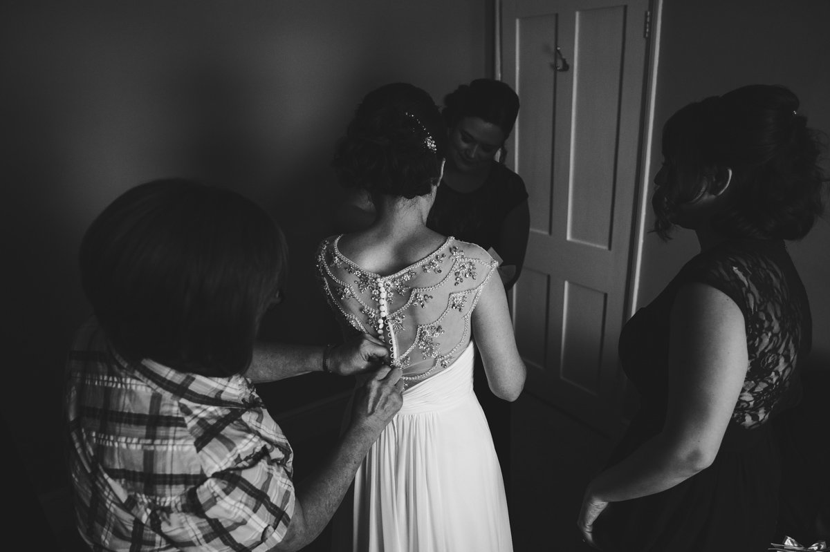 Photography of a Bride helped into her dress before a wedding at Sussex Barn