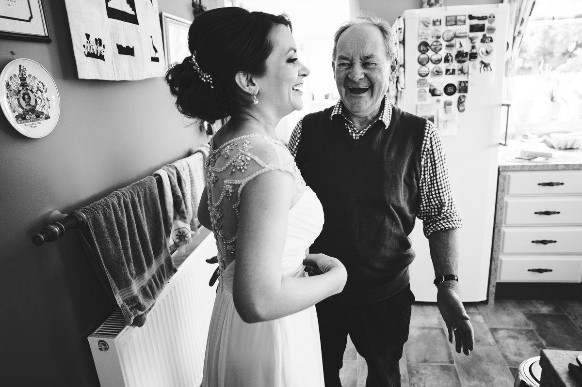 Father of the bride and his daughter laughing together before the wedding ceremony