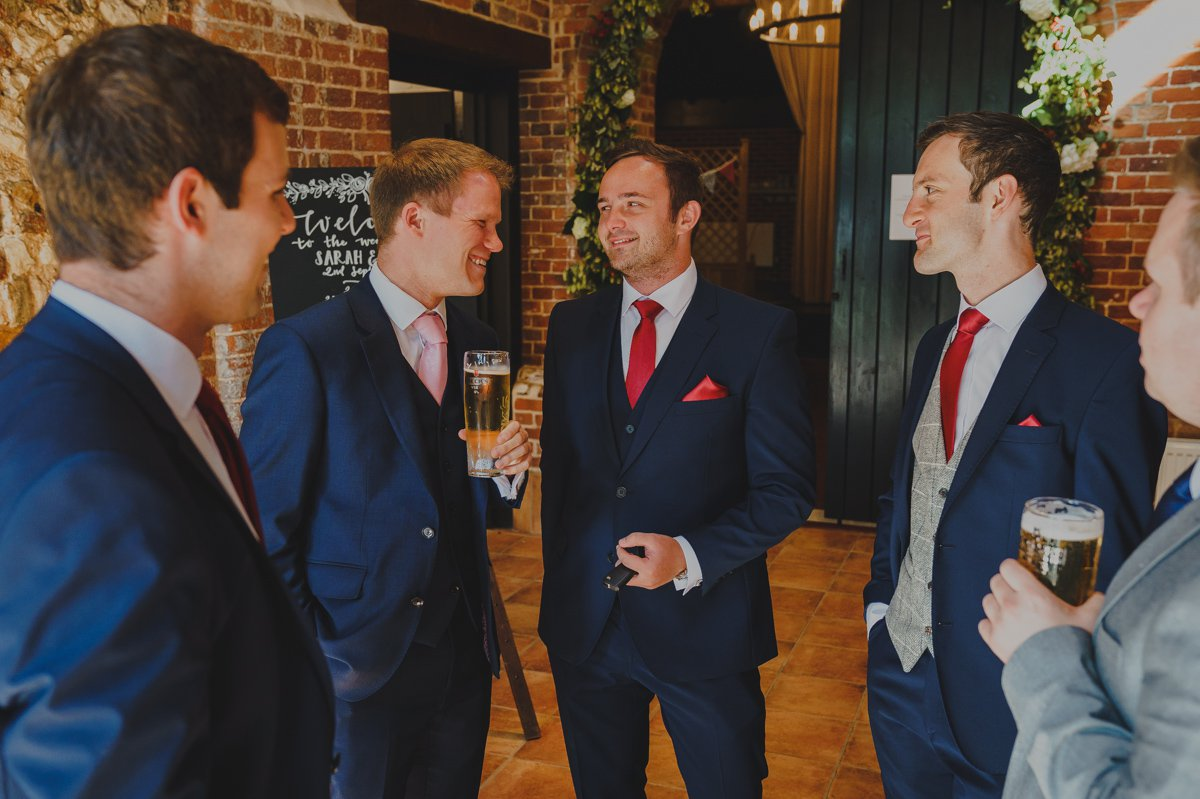 Groom and groomsmen sharing a drink before the wedding