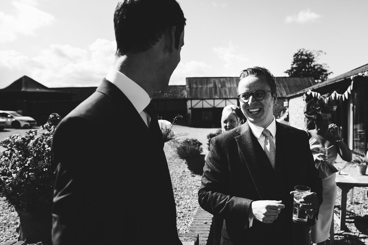 A wedding guest laughs with the groom at a Sussex barn wedding
