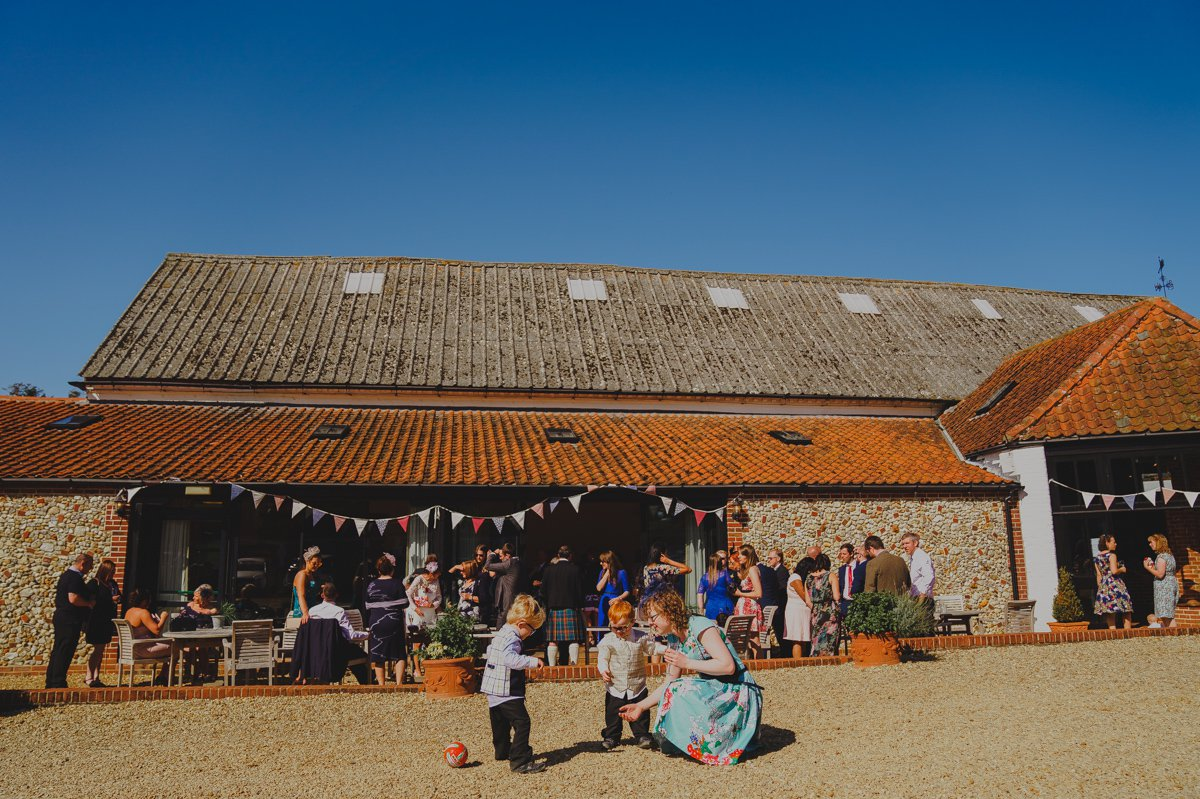 Wedding guests enjoying the sunny weather outside Sussex barn