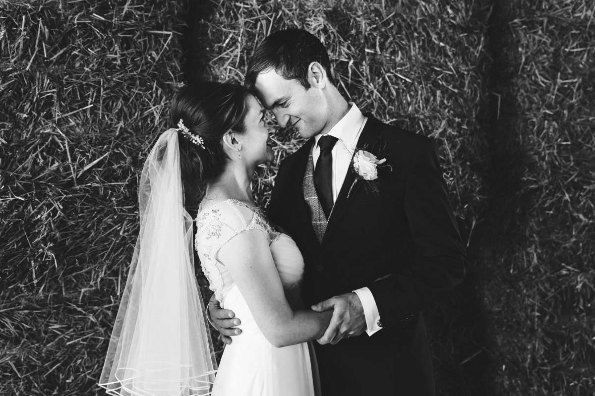 A black-and-white portrait photograph of a bride and groom at a barn wedding in Norfolk