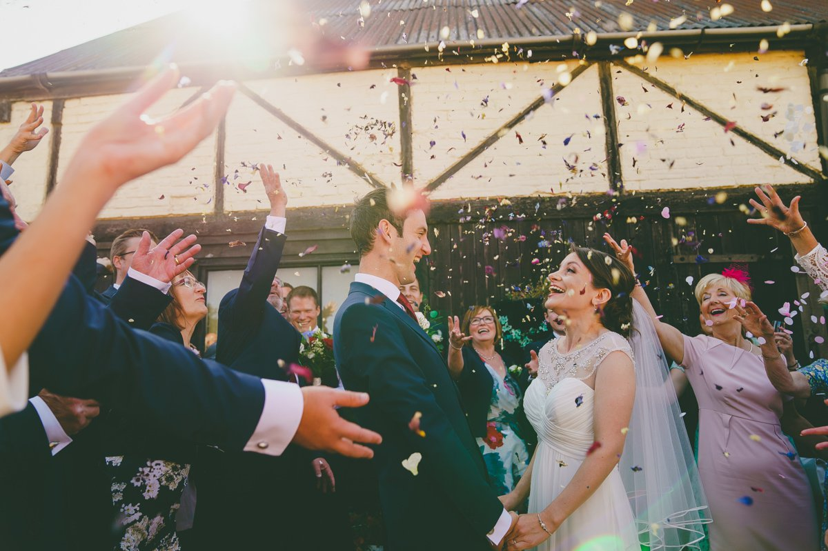 Newlywed couple laughing as they are showered in confetti