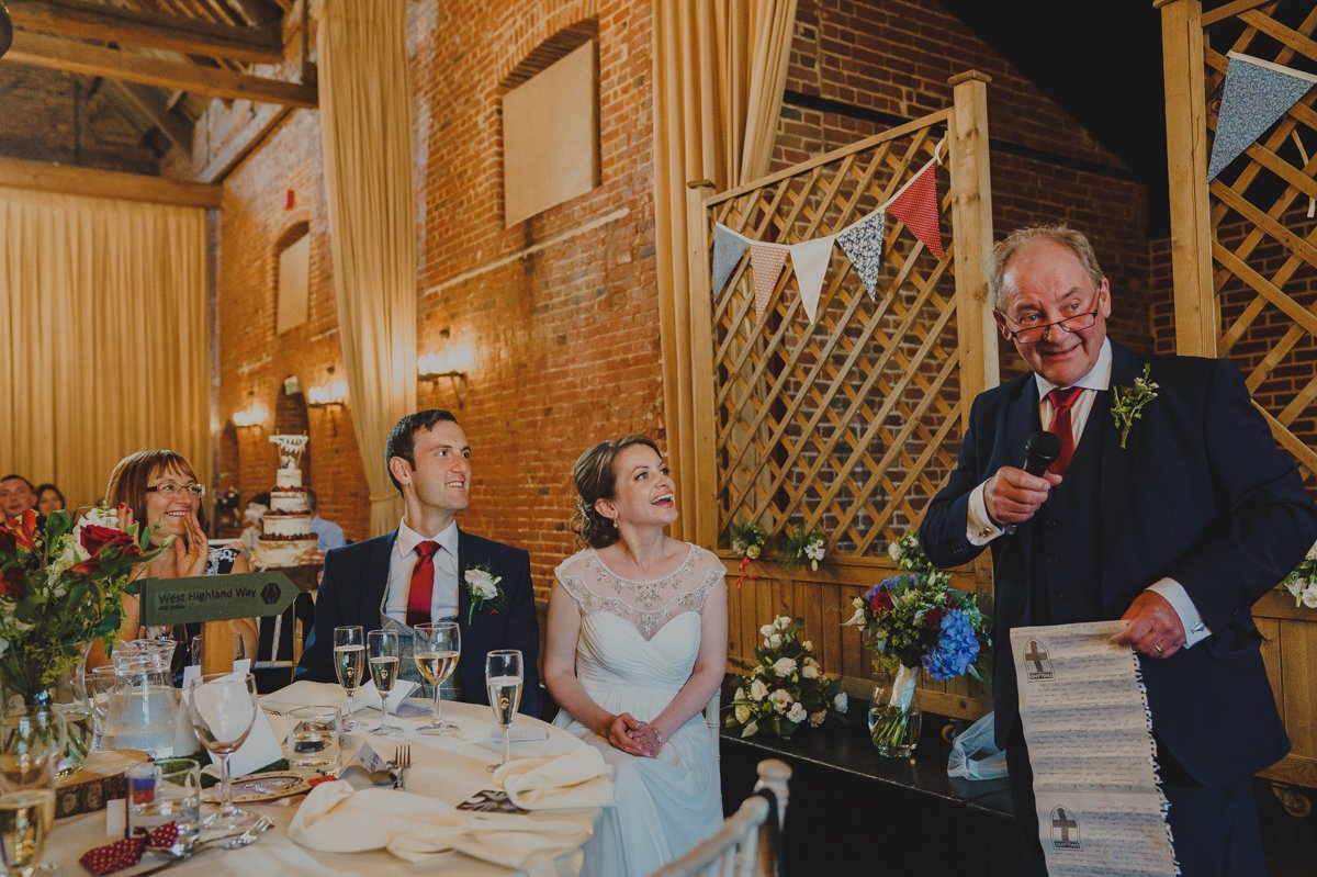 Bride and groom laughing at their wedding speeches at Sussex barn in Burnham market