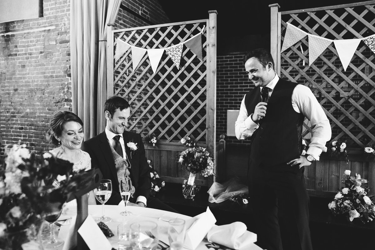 Bride and groom laughing at their best man speech at Sussex barn