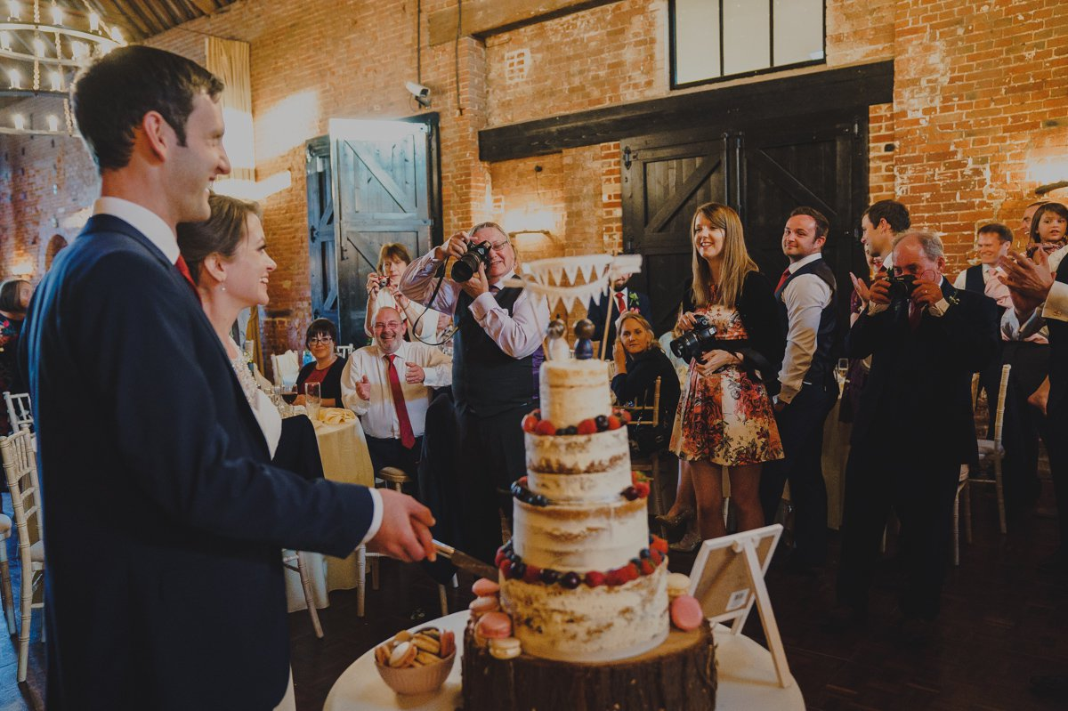 Documentary wedding photograph of bride and groom cutting cake