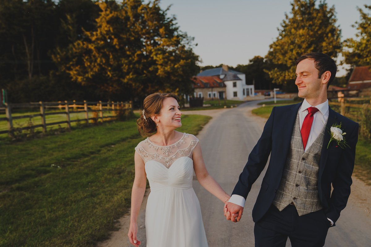 Bride and groom enjoy a romantic stroll at Sussex barn