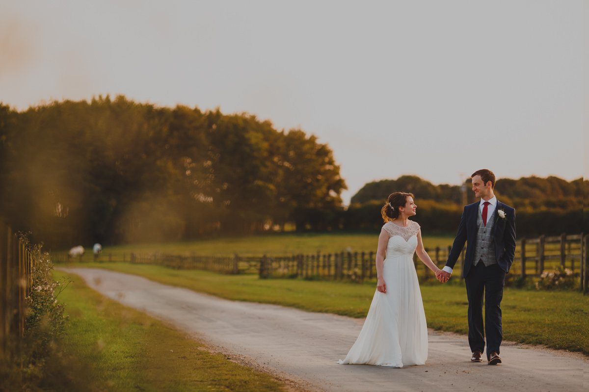 Photograph of a Bride and groom enjoying a romantic walk by sunset