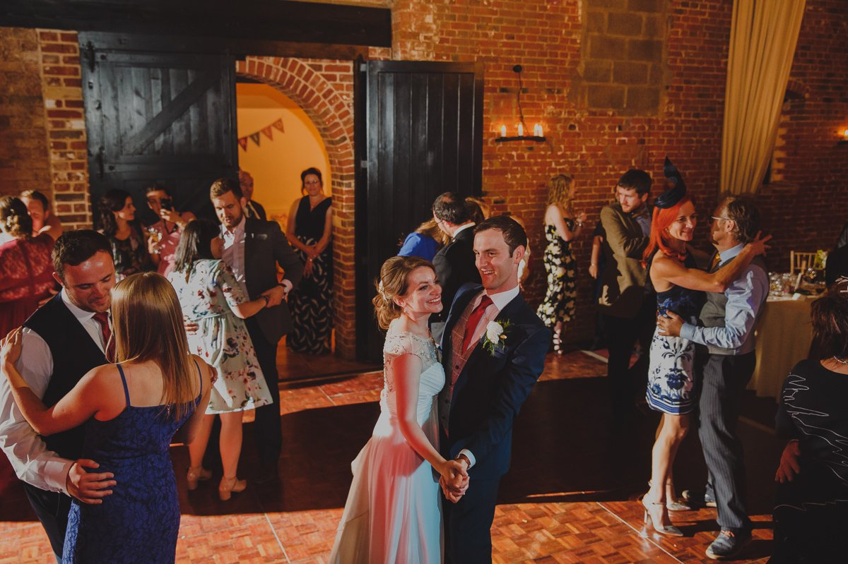 Bride and groom are joined by guests on the dancefloor at their wedding at Sussex barn