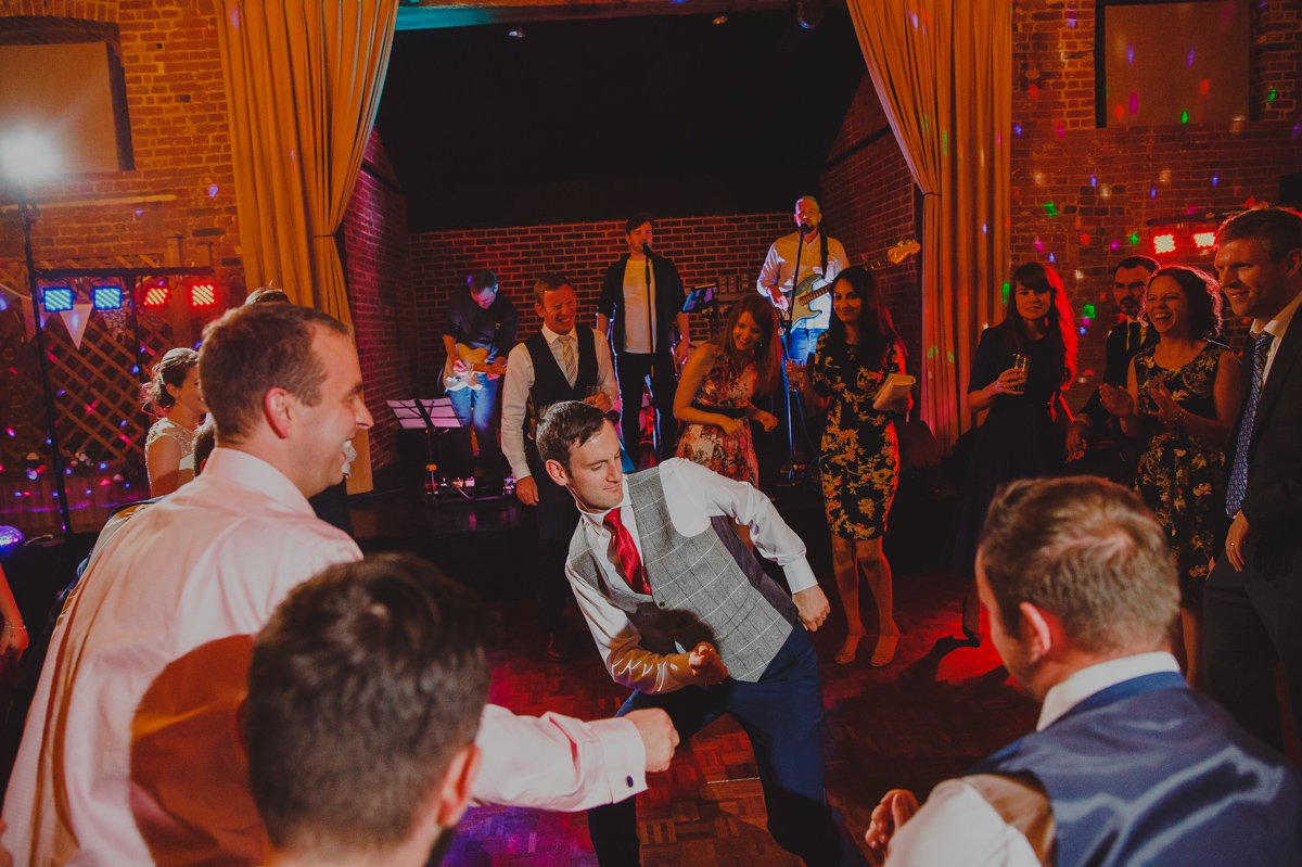 A groom throwing some shapes on the dancefloor