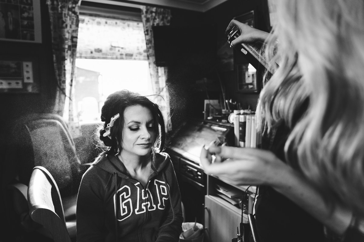 Hair stylist sprays bride with hairspray before her wedding day
