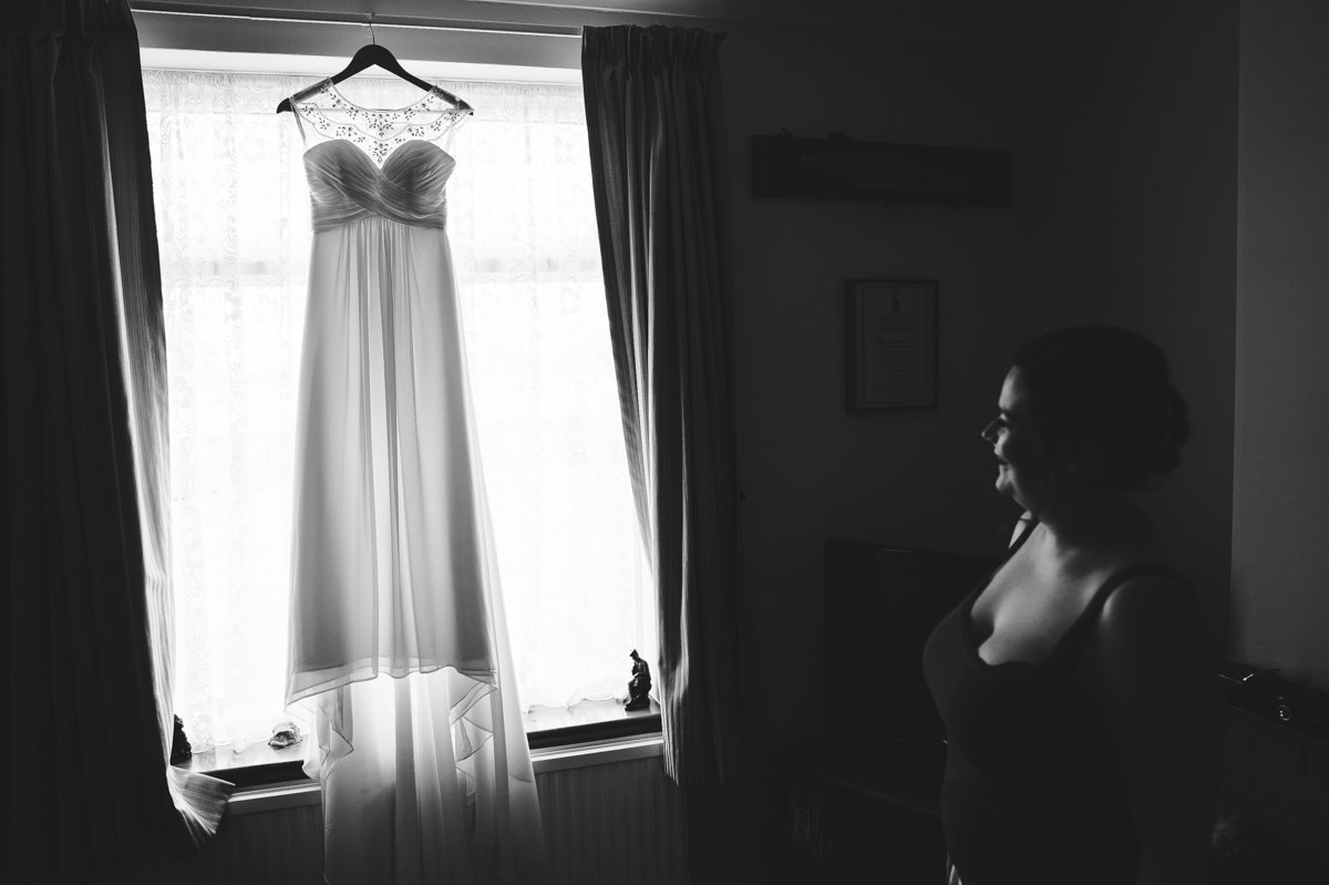 A bridesmaid admires the wedding gown hung in a window
