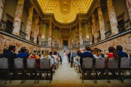 A wedding ceremony in the marble hall at Holkham Hall wedding venue