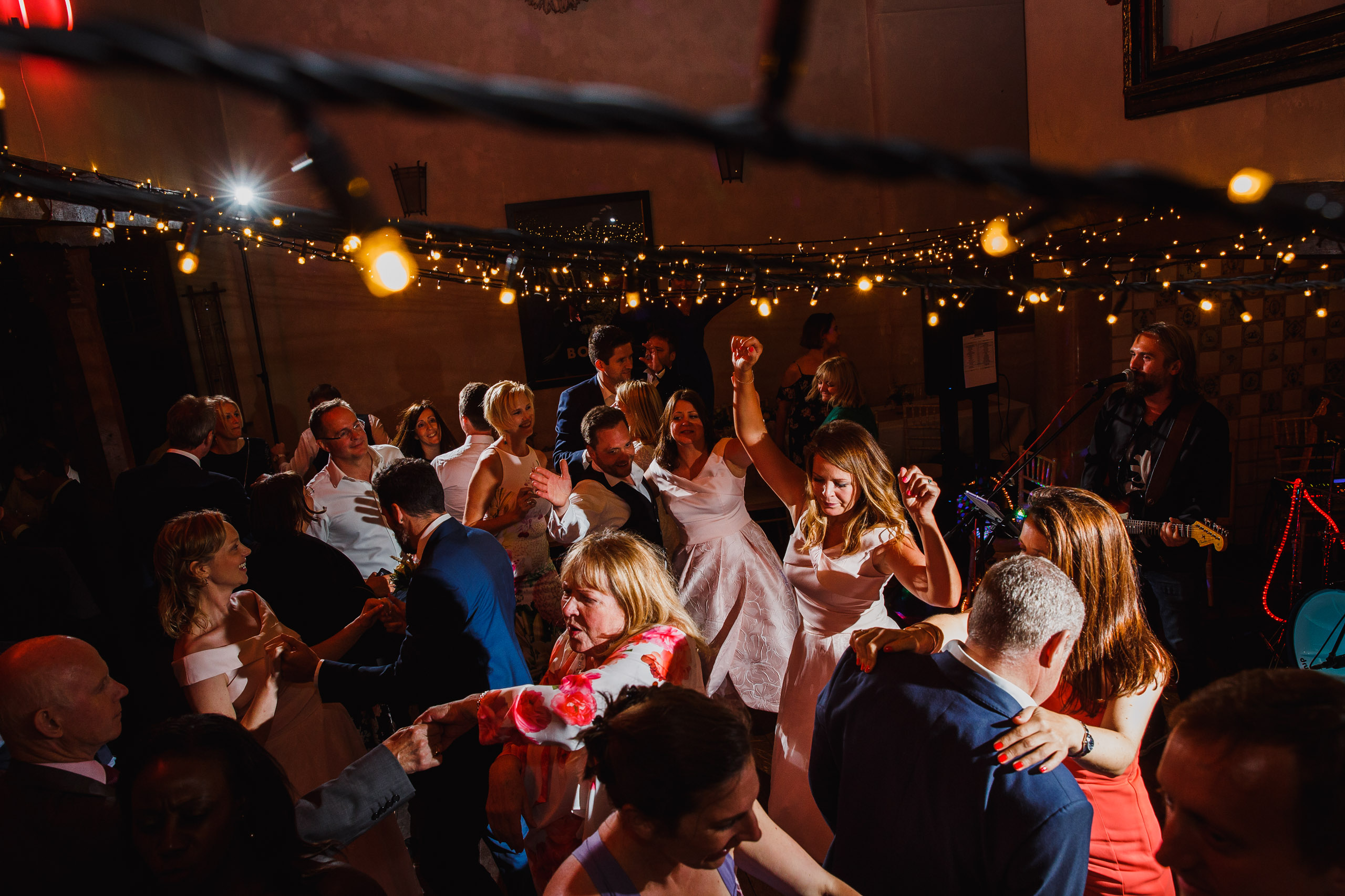 A crowded dance floor at about a voewood wedding