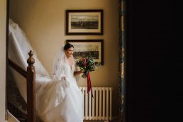 A bride walks down the stairs at Bruisyard Hall