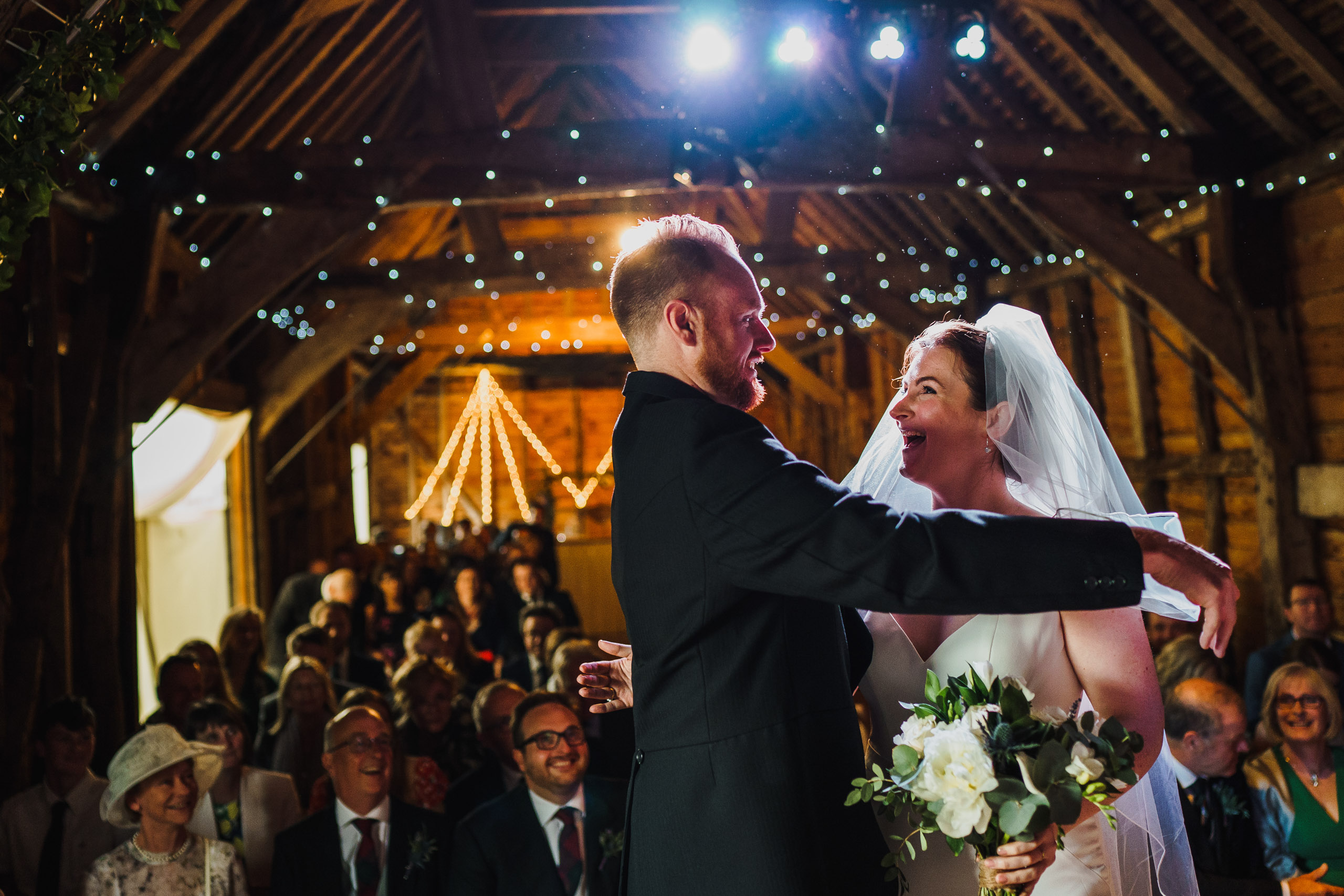 A groom removes the brides veil as they marry at a Norfolk barn wedding.