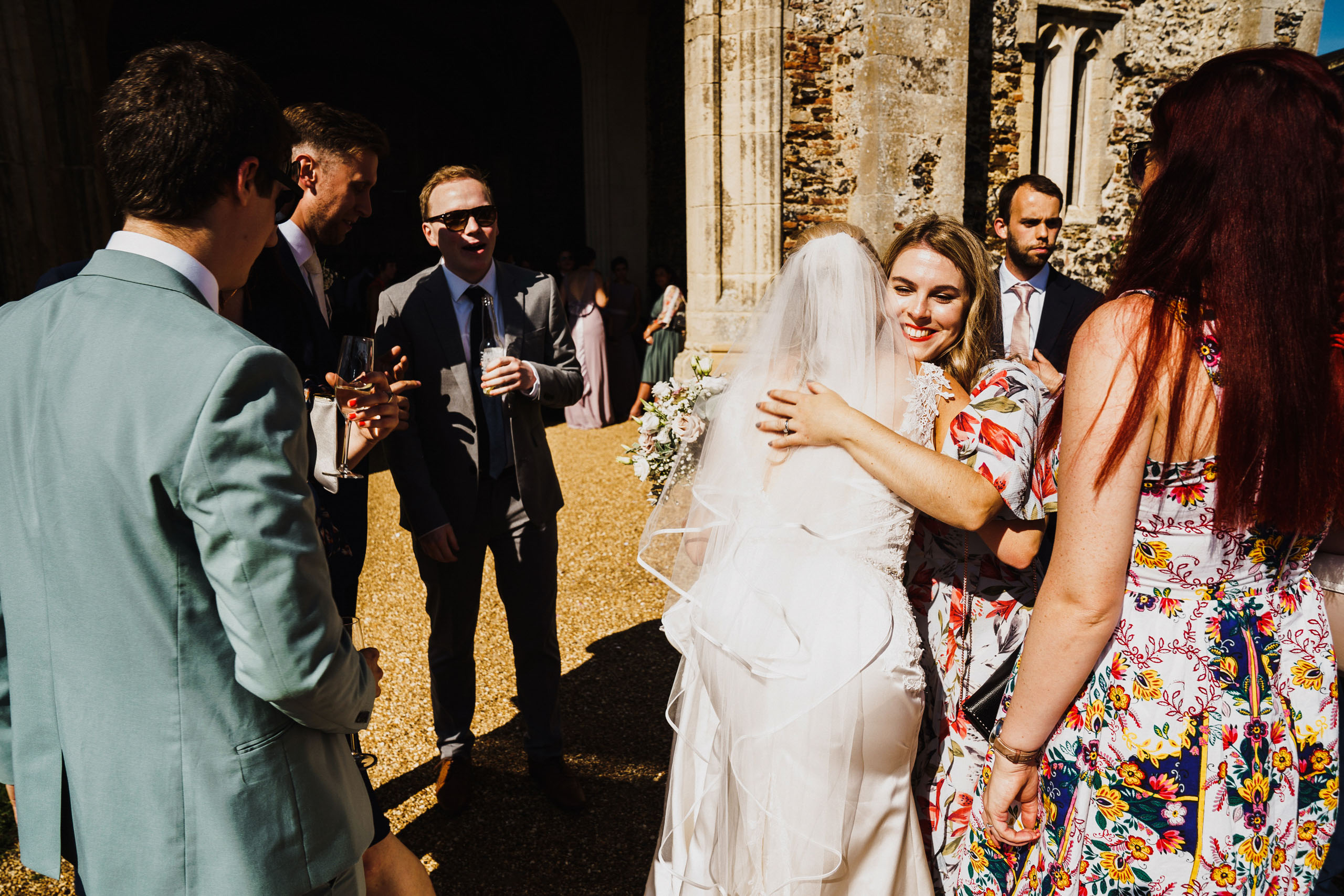 A weding guest and the bride embrace at Pentney Abbey