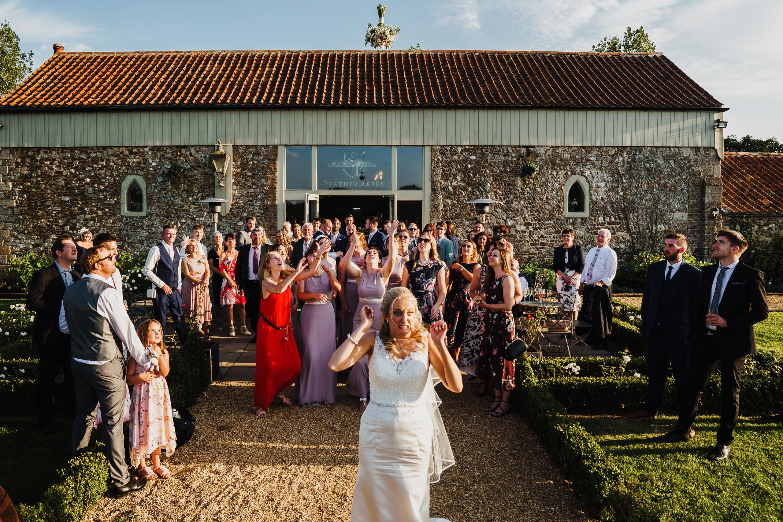 Bride tosses her bouquet outside Pentney Abbey