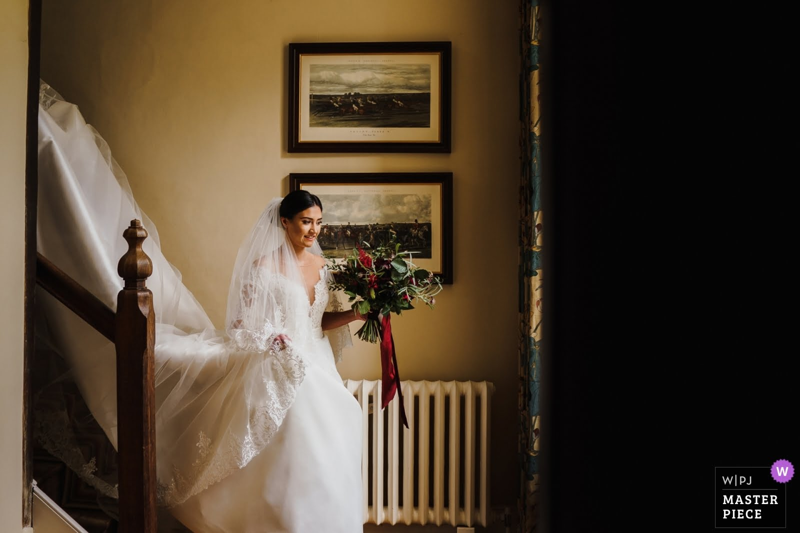 A bride on the stairs at Bruisyard Hall