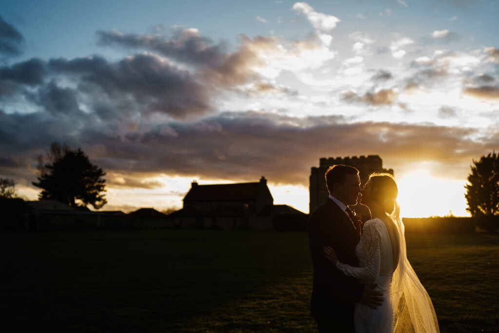 A bride and groom silhouetted against the sun at Pentney Abbey, Norfolk