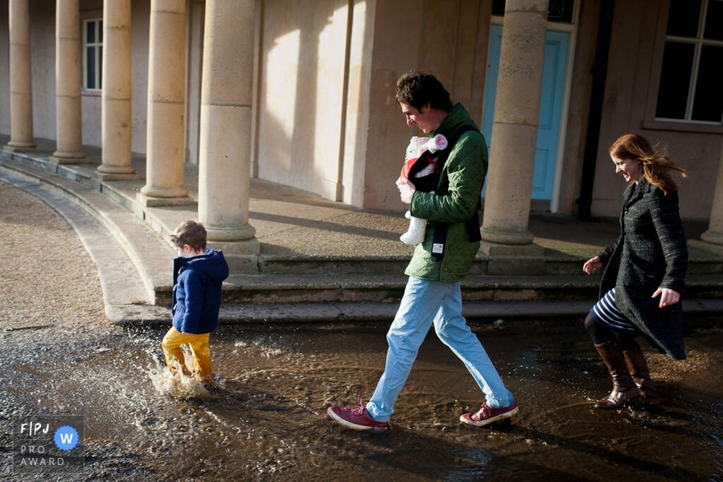 A family splashing in puddles in a Norwich park